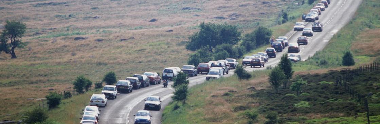 Cars parked on side of road illustrating tourism pressure