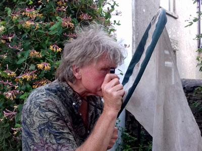 Derek Whiteley looking through lens with net (photo credit Phoebe Whiteley)