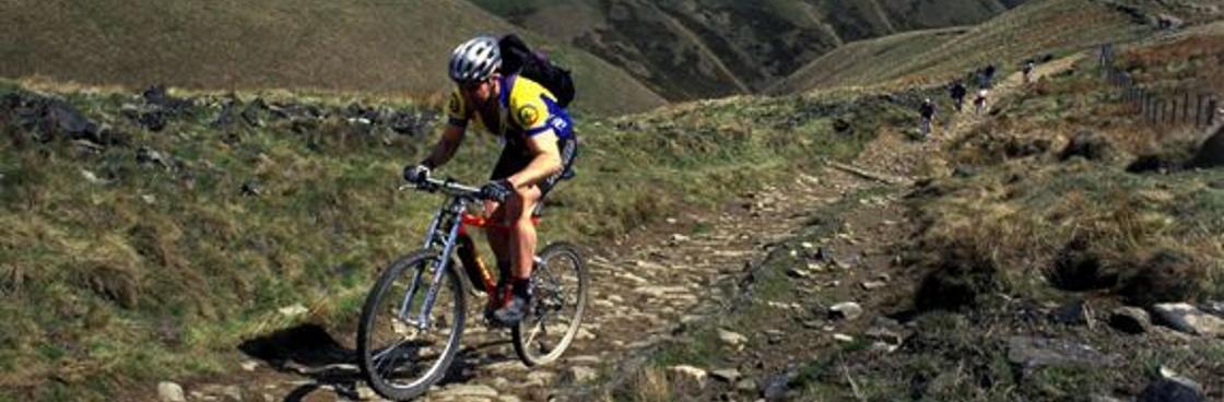 Person mountain biking on a bridleway in the Peak District